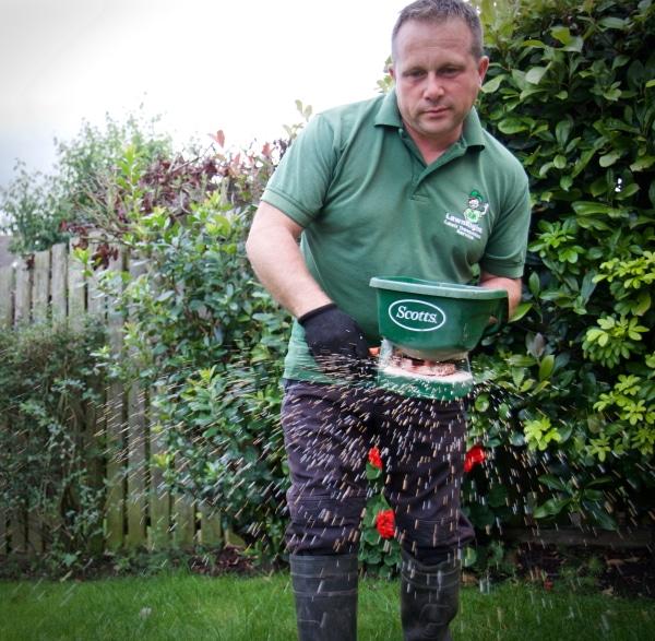 shaun from lawnright applying fertilizer to a lawn